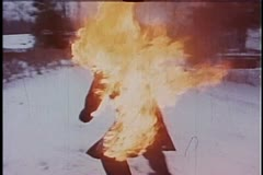 Man on fire crawling through snow towards mansion - stock footage