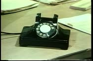 Man holding small notebook talking on rotary phone Stock Footage