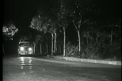Delivery truck speeding down deserted road at night Stock Footage