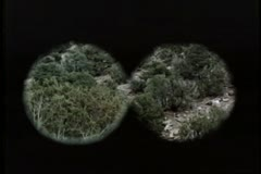 Point of view from binoculars searching mountain side Stock Footage