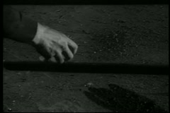 Close-up of hand picking up stick from ground - stock footage