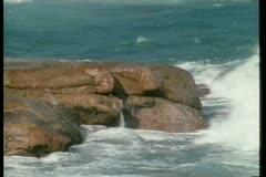 Wide shot of waves crashing against rocks Stock Footage