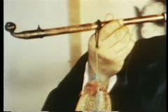 Close-up of hand bringing opium pipe to mouth - stock footage