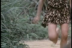Low section of  bare legged boy running through jungle Stock Footage