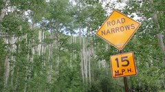Road narrows sign in mountains Stock Footage