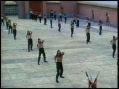 Men practicing martial arts in large courtyard Stock Footage