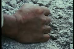 Close-up of a clenched fist picking up gravel Stock Footage