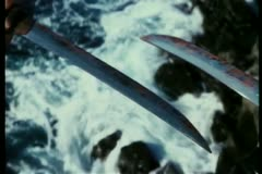 Close-up of bloody daggers held above ocean Stock Footage
