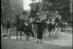 Woman alerting cowboys on horseback Stock Footage