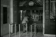 Rear view of couple peaking through gate at railroad station Stock Footage