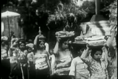 Procession of women carrying food and flowers to a temple Stock Footage