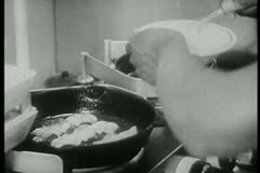 Close-up of cook preparing bacon and eggs on stove Stock Footage
