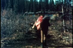 Rear view of man carrying carcass through wilderness Stock Footage
