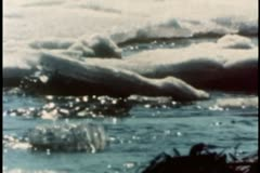 Melting iceberg floating down river - stock footage