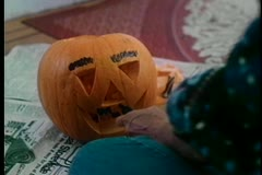 Medium shot of woman drawing teeth on jack o'lantern Stock Footage