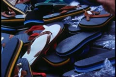 Woman looking through pile of flip flops Stock Footage
