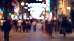 Defocused people (crowd) walking on a night street Stock Footage