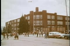 Wide shot of high school students leaving school - stock footage