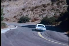 High speed car chase on winding mountain road - stock footage