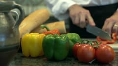 Man cutting red peppers in the kitchen Stock Footage