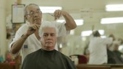 Old barber cutting hair to client in men's beauty parlor - stock footage