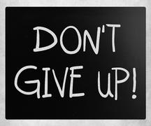 """don't give up"" handwritten with white chalk on a blackboard - stock illustration"