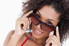 Smiling woman looking aver her sunglasses Stock Photos
