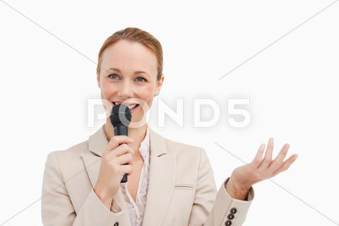 Stock photo of Pretty woman in a suit speaking with a microphone