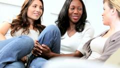 Diverse chatty young girlfriends sitting on modern sofa  Stock Footage