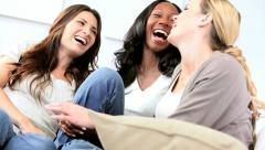 Multi ethnic girls gossiping on couch in modern home  Stock Footage