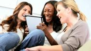 Multi ethnic pretty girls online dating on tablet computer  Stock Footage