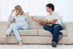 A man is having an argument with his girlfriend while sitting on a couch - stock photo