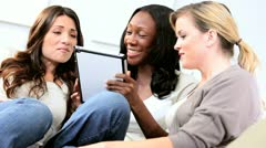 Attractive diverse friends social networking on tablet     Stock Footage