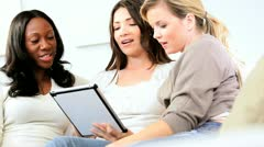 Multi ethnic girls relaxing on couch using touch screen technology  Stock Footage