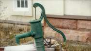1800s water well hand pump near old building Stock Footage