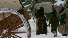 Pulling and pushing handcarts over winter prairie Stock Footage