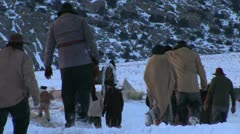 Pulling and pushing handcarts over winter prairie - stock footage