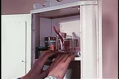 Medium shot of hands groping for toothbrush in bathroom cabinet Stock Footage