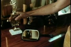 Medium shot of man picking up hand mirror on trophy table Stock Footage