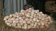 Stock Video Footage of PAN huge egg pile to seller sitting under umbrella African market
