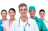 Stock Photo of Attractive doctor with his team behind him
