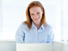 Self-assured business woman working on a laptop computer - stock photo