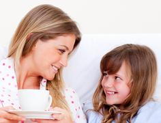 Attentive mother and her daughter drinking coffee lying in bed - stock photo
