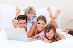 Enthusiastic family buying online lying down on bed Stock Photos