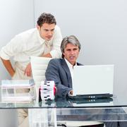 Confident manager helping his colleague work at a computer Stock Photos
