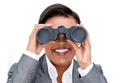 Self-assured businesswoman looking through binoculars Stock Photos