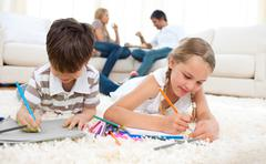 Concentrated siblings drawing lying on the floor - stock photo