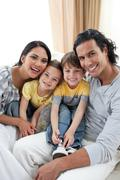 Portrait of an affectionate family sitting on sofa - stock photo