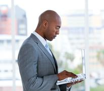 Stock Photo of Portrait of an assertive businessman working at a laptop