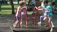 Stock Video Footage of Children Playing at Playground, Kids, Girls Spinning, Rotating on Merry-Go-Round